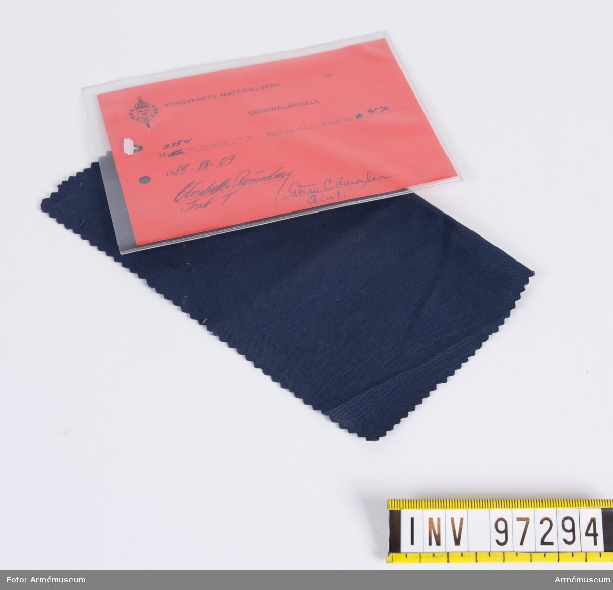 """Vidhängande modellapp med text: """"Försvarets materielverk. Originalmodell. M 7354-311000-7. Poplin till blus m/47 1985-08-07. Elisabeth Rönnberg IntT, Göran Olmarker QInt."""""""