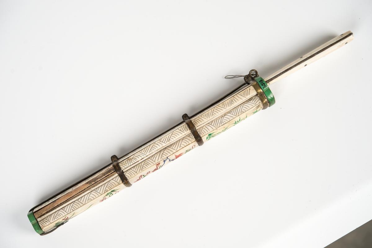 Från fregatten Vanadis världsomsegling 1883-1885. Kina. Fodral av elfenben med dekor i grönt och rött, hållet av metallstomme. Försett med urtag för kniv och två pinnar. Beslag upptill och nedtill av grönfärgat ben Kniv långsmalt blad, eneggat. Skaft av elfenben.