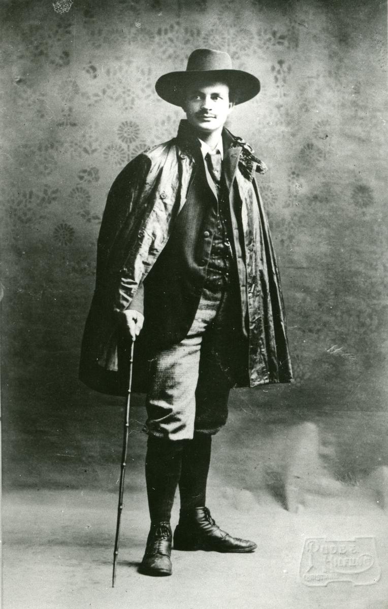 Mann oppstilt for fotografen m/hatt, spaserstokk og regnkappe over skulderen. Portrett av Haakon Garaasen (6/7 1887 - 1957)