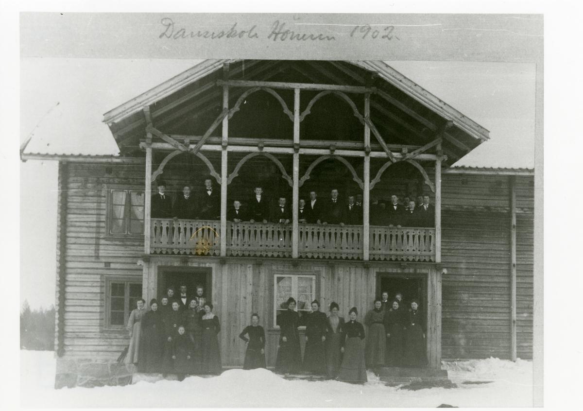 Høneren Begnadalen. Elever på danseskole står utenfor et hus. Damene står på bakkenivå, og karene står på verandaen i andre etasje.