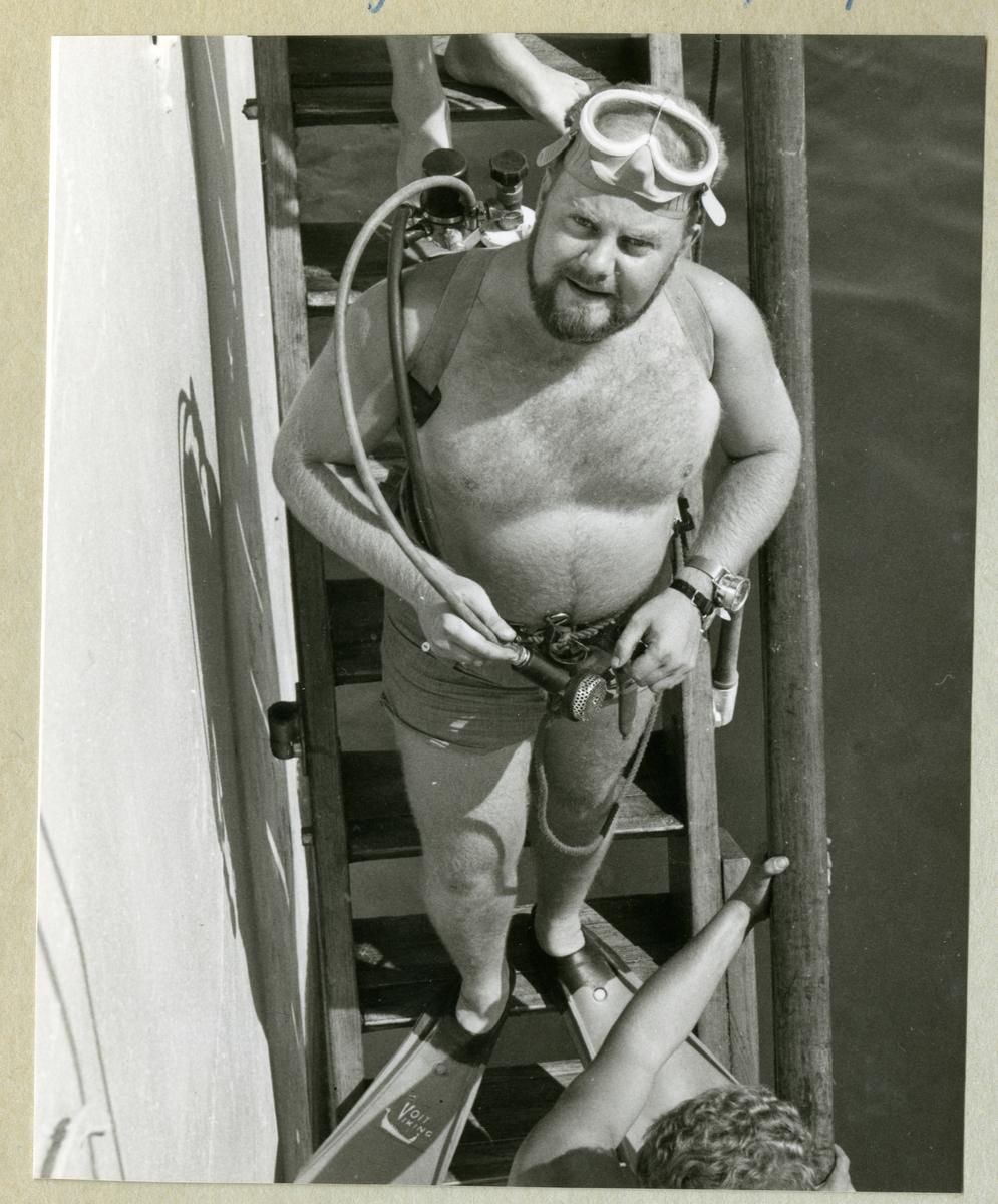 Bilden föreställer en besättningsman i dykarutrustning under minfartyget Älvsnabbens långresa 1966-1967.