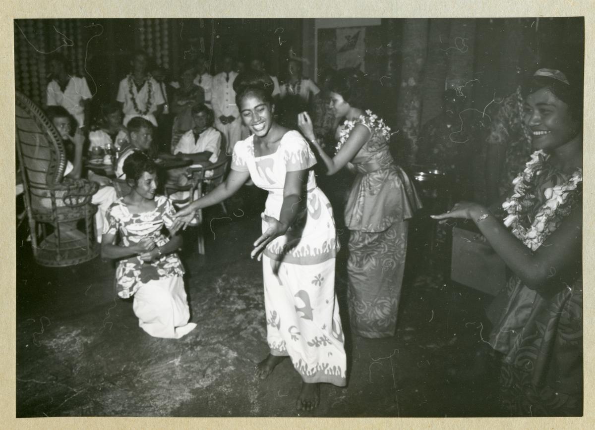 Bilden föreställer fyra kvinnor som framför en dans. I bakgrunden syns uniformsklädda män som åskådare. Bilden är tagen i Samoa i samband med minfartyget Älvsnabbens långresa 1966-1967.