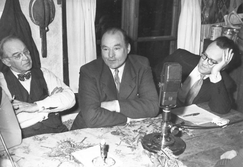 Per-Martin Hamberg och byggmästare Herman Henriksson lyssnar till en rolig historia som byfogden Ragnar Johansson, Utterbyn, berättar. Herman Henriksson Västanvik sitter till vänster. (Enligt kommentar från digitaltmuseum.se)
