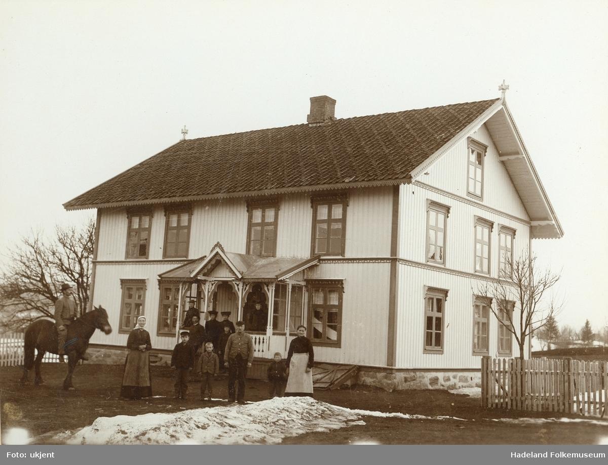 En gruppe mennesker og en hest er oppstilt utenfor et bolighus