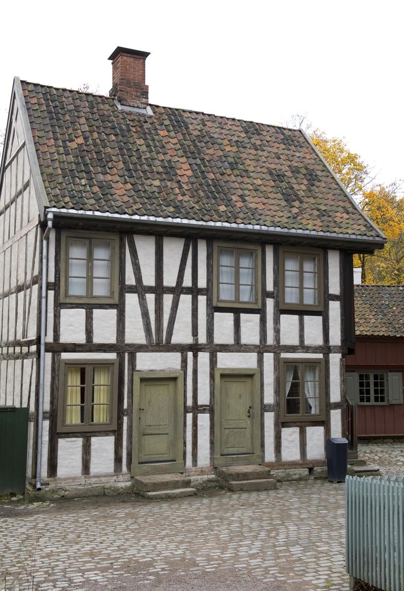 1800 Huset er oppført i utmurt bindingsverk og har to etasjer og loft. I første etasje var det en leilighet som besto av stue, kjøkken og kammers, i annen etasje en leilighet på tre rom og kjøkken. I 1891 eide den 50 år gamle kommandersergeant Hans Andersen gården. Han bodde  i leiligheten i annen etasje sammen med kone og tre sønner, som var hhv bokbindersvenn og malersvenn. I første etasje bodde lagerformann med fire mindreårige barn. Husholdet besto ellers av tjenestepiken Nicoline Amalie og Anne Marie Larsen Due som var sypike og losjerende. Anne Marie var delvis forsørget av fattigvesenet.   Norsk folkemuseums guidebok,  1996