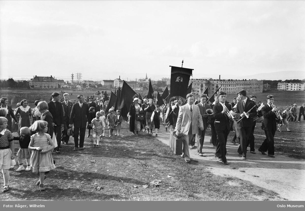 1. mai-feiring, opptog, menn, kvinner, barn, musikkorps, faner, flagg, boligblokker