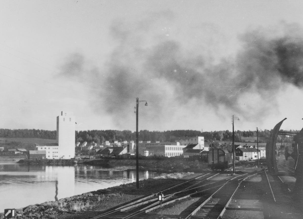 Utsikt fra fyrbøterplassen på damplokomotiv type 63a idet toget kjører inn på Steinkjer stasjon.