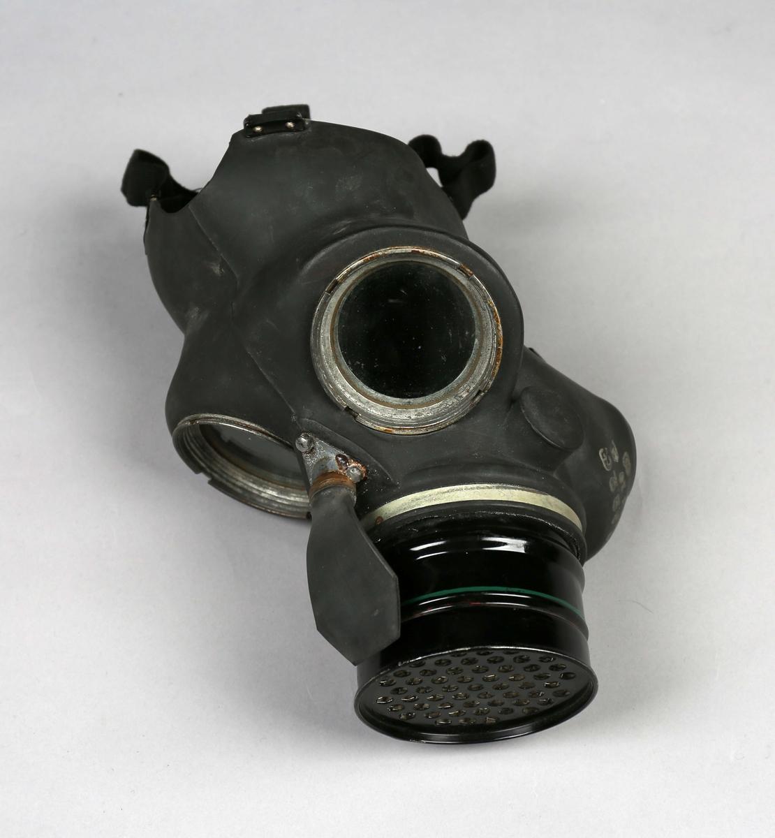 Gassmaske i tøyveske. Gassmaske i gummi med filter. Festes til ansiktet  med seks elastiske reimer/stropper. Masken er en ansiktsmaske med sirkelrunde glassflater som synsfelt.