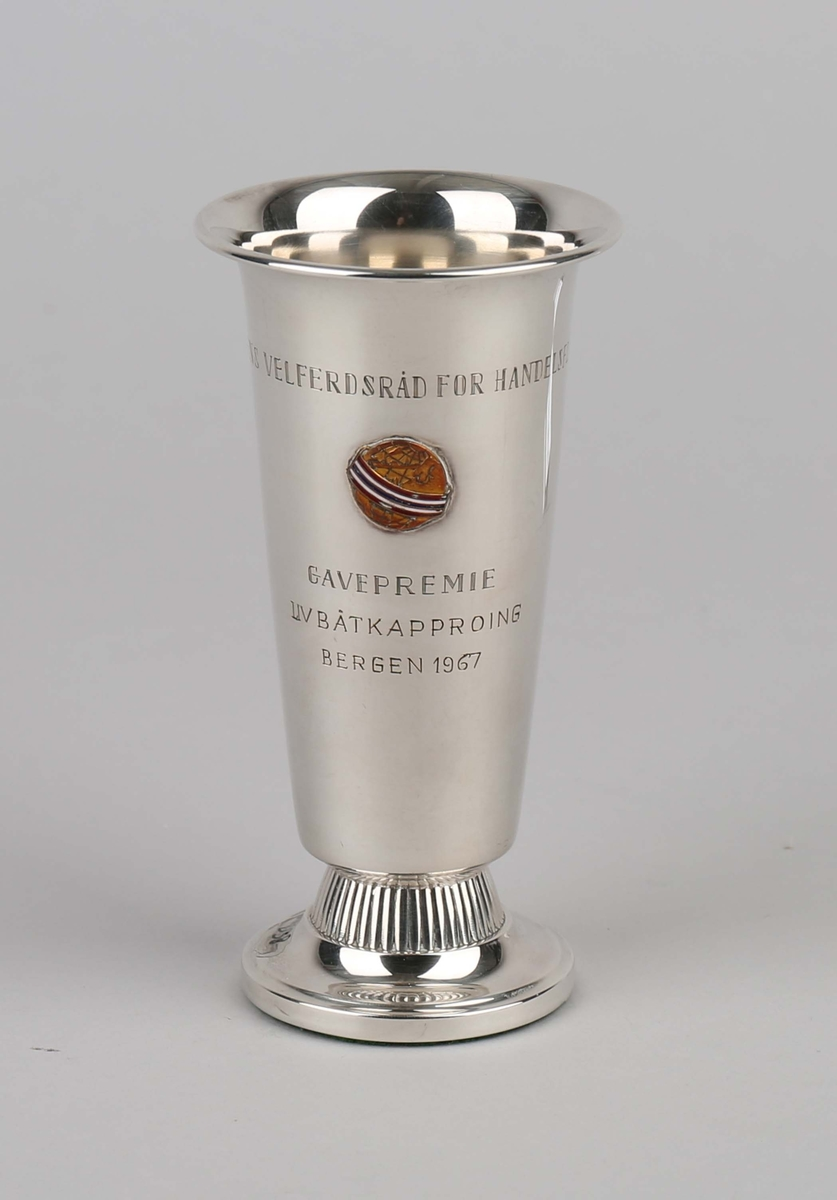 Sølvpokal fra Statens Velferdsråd for handelsflåten. På sokkel og med emaljert merke i front.