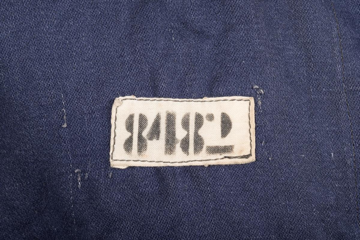 Jakken er sydd i mørkeblått tykt bomullsstoff. Den har påsydd et hvitt bånd som går trekvart rundt venstre arm, med en nedadgående V under. På høyre bryst er det påsydd en stofflapp med fangenummeret 8482, som identifiserer eieren av jakka som Odd Franz Schrøder.