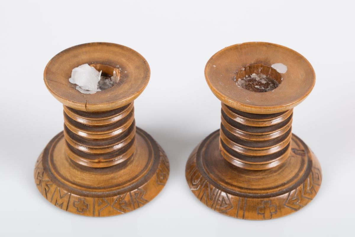 Et par dreide lysestaker i tre. Lysestakene er runde i formen. Nederst på foten er det risset inn latinsk tekst.