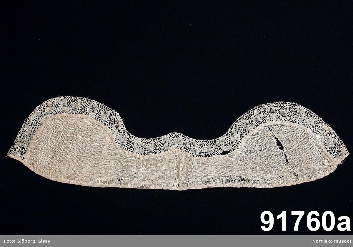 a. Katalogkort: Mösstycke af grof gles linneväf med knypplad spets av lingarn.  Stycket format med 2  uddar och en liten spets mitt fram, spetsen ca 4 cm bred följer formen. Spetsen är av en äldre, 1700-talet, typ av knypplad spets och kan vara från Vadstena. /Berit Eldvik 2007-11-05