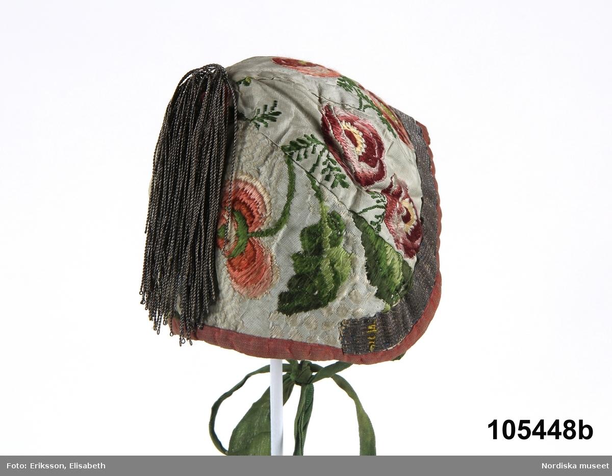 Doppåse a. med mössa b.  a. Doppåse av ljusgrå sidenbrokad med slingrande blommönster i flera nyanser rött/rosa, blått, och grönt med inslag av gult och vitt, ett mönster från omkr. 1750 som sannolikt ursprungligen varit en klänning. Upptill är påsen något ringadd och hoprynkad med en kant av rosa sidenband som avslutas i knytband bak, sprund i ryggen. I nederkanten dekorerad med en  slingerbård av guldtråd i luftmaskor. Påsen fodrad med vit flossad väv av bomullskypert.  b.  /Berit Eldvik  200-01-16