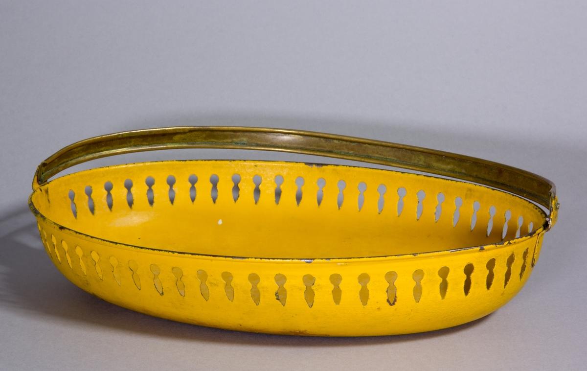 Brödfat av plåt med fällbart handtag av mässing, ovalt, målat i gult, hålmönster längs kanten.