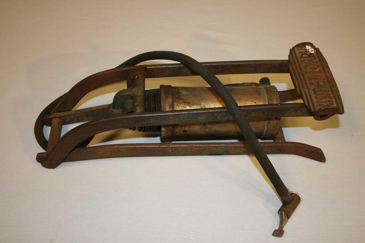Messingsylinder montert i jernstativ med pumpemekanisme. Gummislange med munnstykke til dekkventil.
