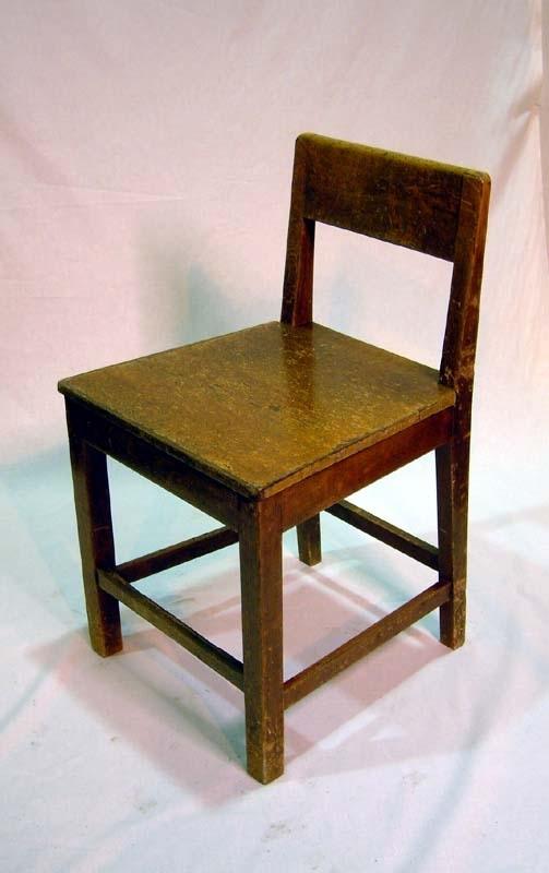 Stol helt i trä. Fyra ben, släta, bakbenen lutar svagt bakåt. Tvärslåar mellan varje stolsben. Slät och platt sits. Ryggstödet märkbart lågt. Slät och enkel ryggtavla. Målad med brun målarfärg som blivit avskavd på flera ställen.