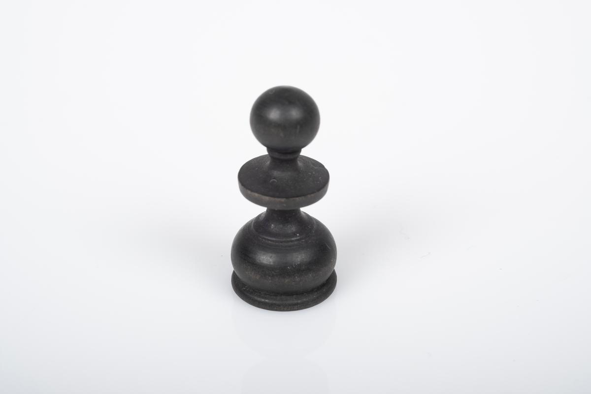 Sjakkbrikke (bonde) av tre. Brikken er dreid og malt/lakkert svart.