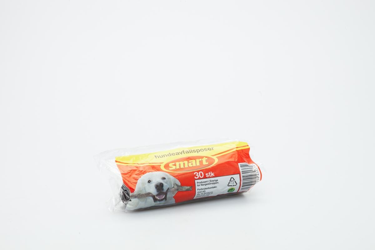 En pose med et motiv av en hund. Inne i posen er det en rull med sorte hundeposer i myk plastikk  Gjenstanden er samlet inn i forbindelse med Hundeprosjektet 2006-2007 Husdyr på museum - Et fellesprosjekt i Akershusmuseet 2007