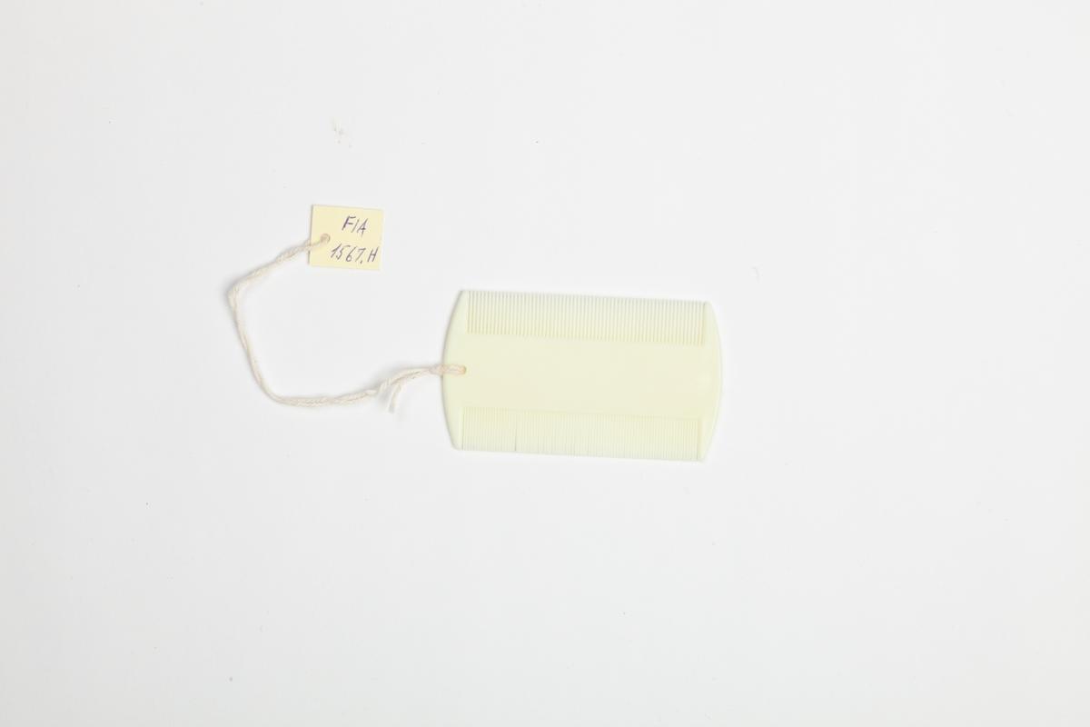 En kam i hard plast med to sider med tettsittende tenner. På den ene siden er kammens tenner litt mer tettsittende enn på den andre. Kammen er i en kremhvit farge