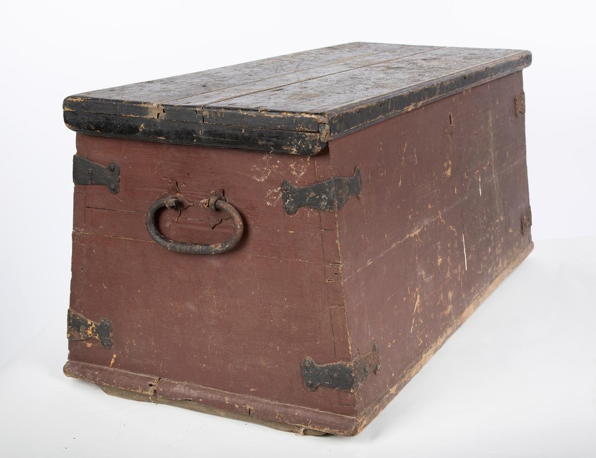 Sitte- og oppbevaringsmøbel ombord i skip. Håndtak på sidene. Avsmalnende mot toppen. Jernbeslag. Todelt fargekode. Lokk utført i svart, mens kassen er malt i burgunderrødt.