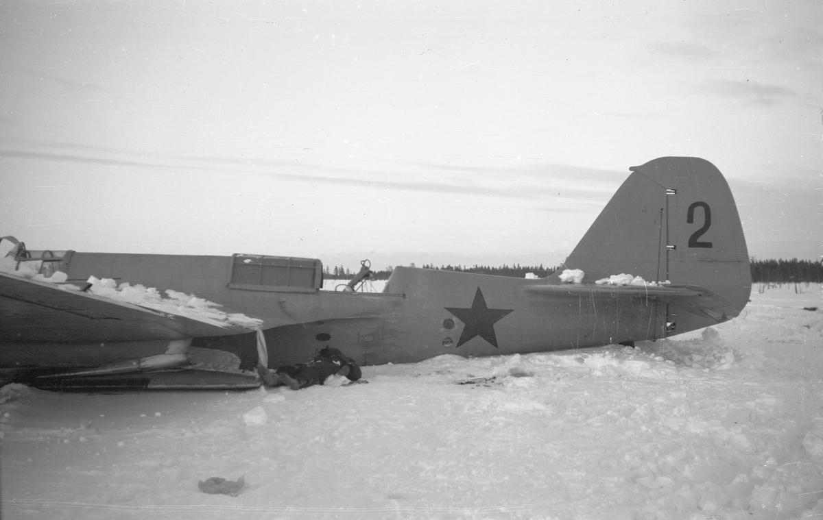 Nedskjutet sovjetiskt bombflygplan SB-2 ligger på ett fält vid Svenska frivilligkåren i Finland, F 19. Mitt- och stjärtparti.