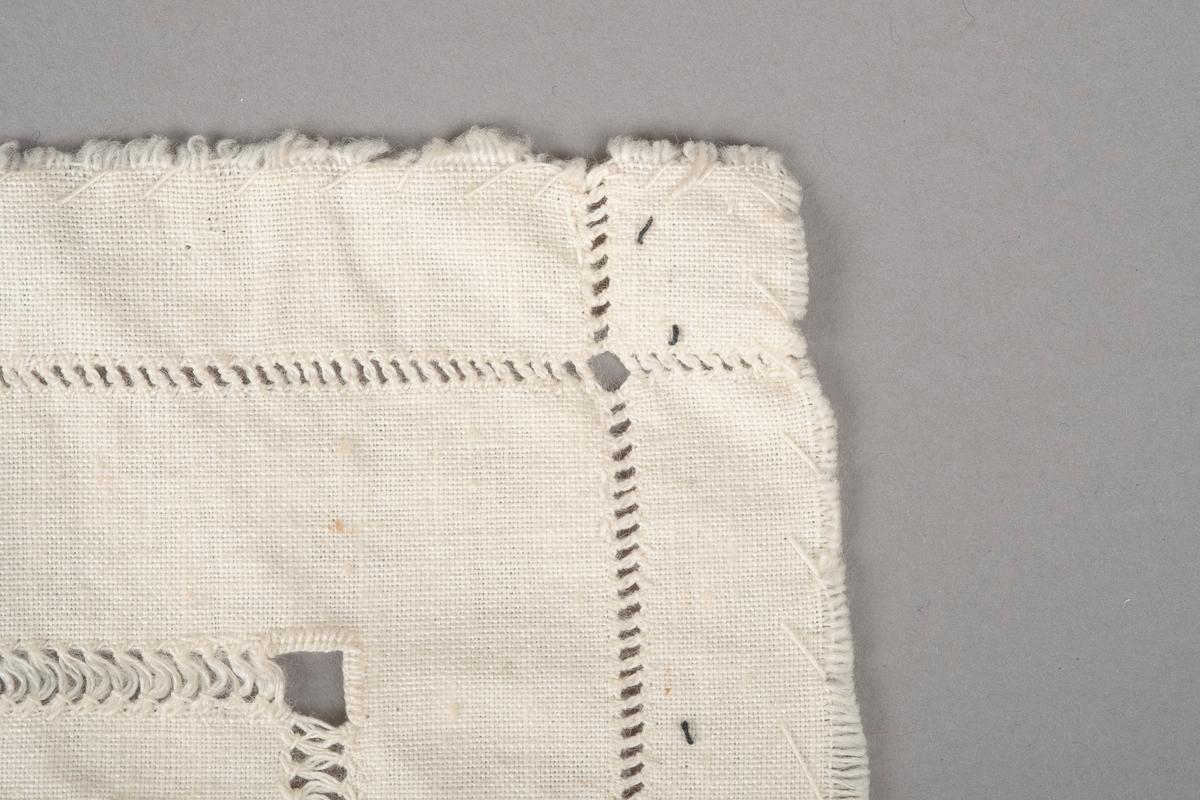 Et rektangulært lite bordduk med hull- og sammentrekkssøm. Kantene ser ut til å være revet og ikke klipt. Kantsømmen er ikke tett. Det er usikkert om hensikten er å hindre kantene i å rakne eller om det bare er pynt. Det er brodert tekst i midten. Flere steder på duket er det små svarte sømmer.