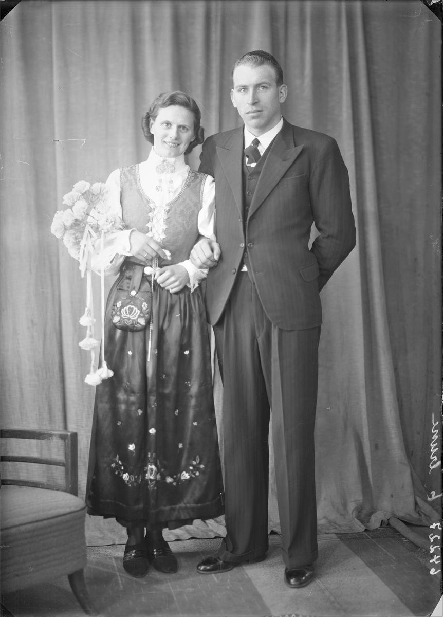 Portrett. Brudebilde. Ung mørkhåret kvinne i nasjonaldrakt og ung mann i mørk dress, lys skjorte, mørk vest og mørkt slips. Brudepar. Bestilt av Lars Hausken. Nordø. Karmøy.