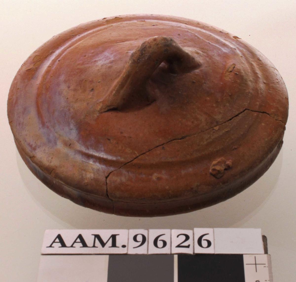 Lokk til stekepanne. Hollandsk. Leirtøy - rødbrunt med blank rødbrun glasur. Oversiden er hvelvet med en profillinje langs kanten og en hankering på toppen. Undersiden har sotbelegg og en skålform.