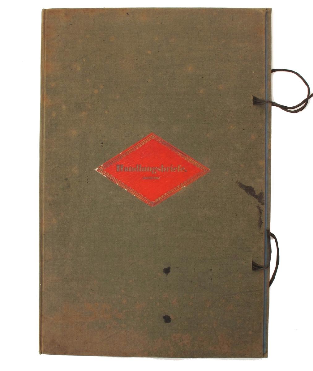 Brevmappe med stiv lerretsperm, rød tureformet etikett med ovenstående tekst i gull. To brune knyttebånd.  Innv. blått papir.  Inni ligger to gamle papiromslag fra arkivet.