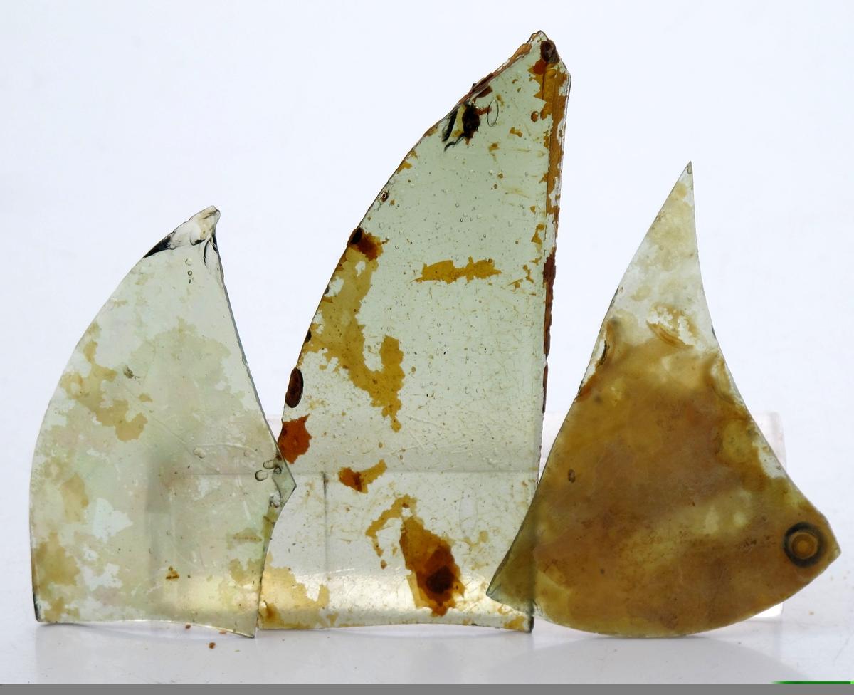 """Biter av vindusglass, fra """"Fredensborg.""""  Grønt glass. tildels med brune flekker. Tilsammen 55 stk."""