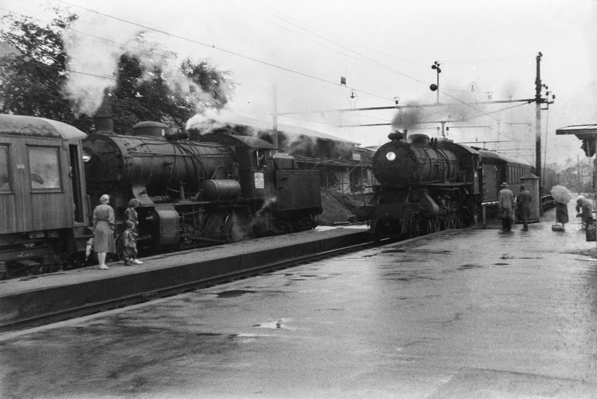 Kryssing på Minde stasjon. Til venstre damplokomotiv type 33a nr. 300 med persontog. Første vogn i toget er litra Bo4b type 3 nr. 968. Til høyre persontog med damplok type 31a nr. 319.