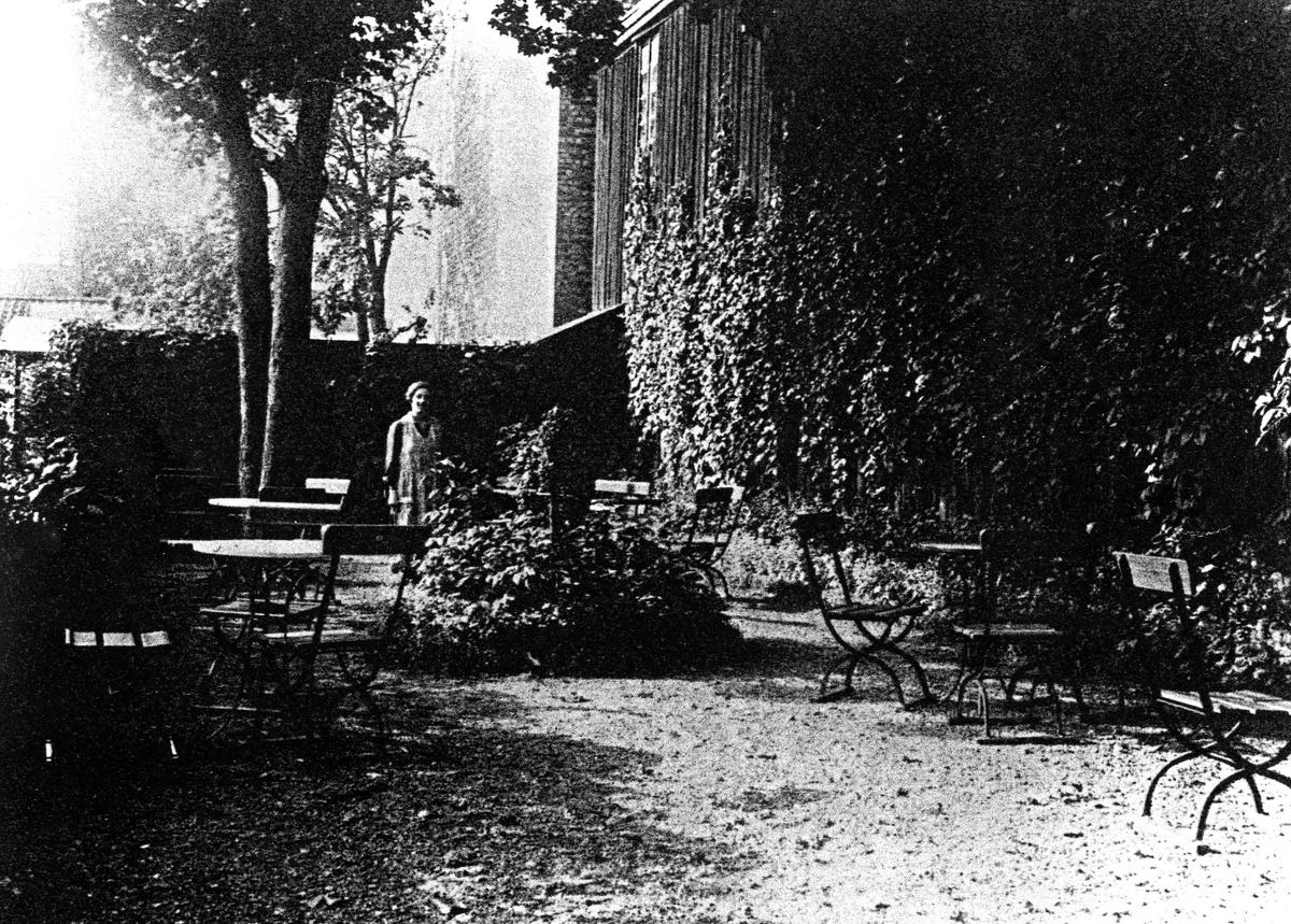 Bilden visar Ljungblads konditoris gårdsservering, i bakgrunden bland bord och stolar ses Judit Ljungblad stående.