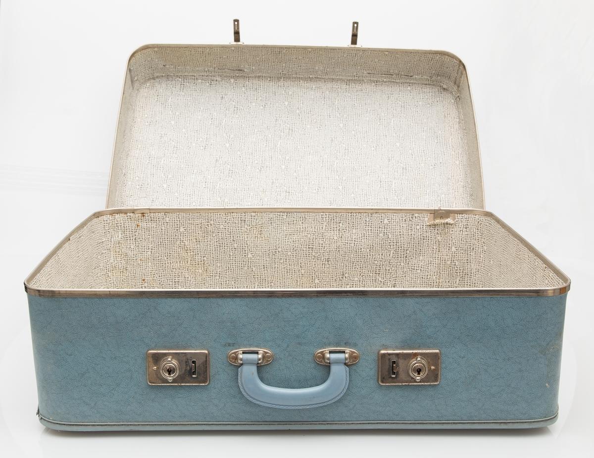Lys blå koffert med to låser med store beslag. Metallkant på lokket. Bærehåndtak.