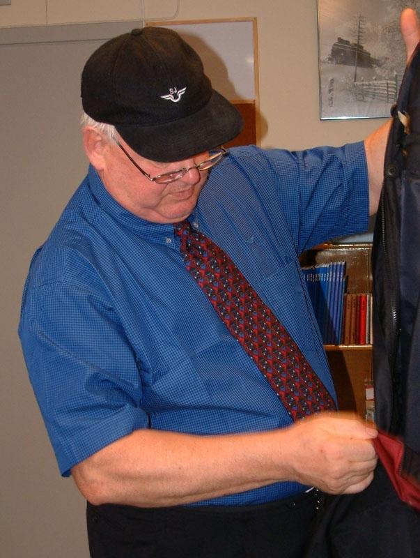 Flerfärgad s k säkerhetsslips med mönster i rött, blått och svart. Försluts med kardborrband i nacken.
