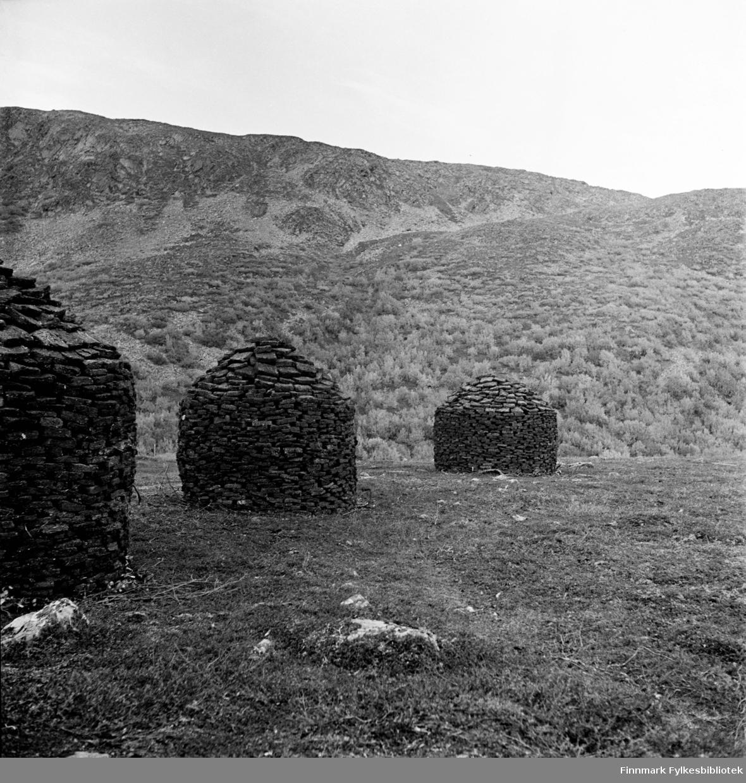 Torvsete utenfor Kjøllefjord, langs den gamle Kjøllefjordveien, fotografert i 1940. Tørking av torv til brensel ble stablet på denne måten slik at regnet skulle renne av og formen kalles et torvsete. På den treløse kysten var torv brukt til brensel i mer enn tusen år. Torv med mindre enn 25 % fuktighet har brennverdi som bjørkeved. På næringsfattige nedbørsmyrervokser torvmose (sphagnum). Mangel på luft gjør at planterestene ikke råtner. De omdannes gjennom en fortorvingsprosess til en svart og gjørmeaktig masse som kalles myrtorv. På bilde FBib.18010-034 og FBib.18010-036 sees to gutter som frakter denne torva på trillebårer tilbake til Kjøllefjord, samtidig med at de driver en geiteflokk som har vært på beite tilbake til Kjøllefjord.