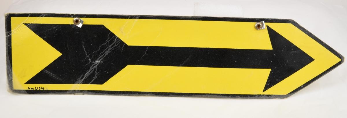 Två stycken skyltar av laminerat papper i kvadratisk form med ett pilformat avslut. Skyltens botten är gulfärgad och motivet består av en svart pil. Skylten omges av en svartfärgad ram. Skyltens övre kant har två hål där det sitter en metallnit i vardera hål. På baksidan av nitarna sitter avklippta metalldelar som i normalskick haft en upphängningsfunktion.