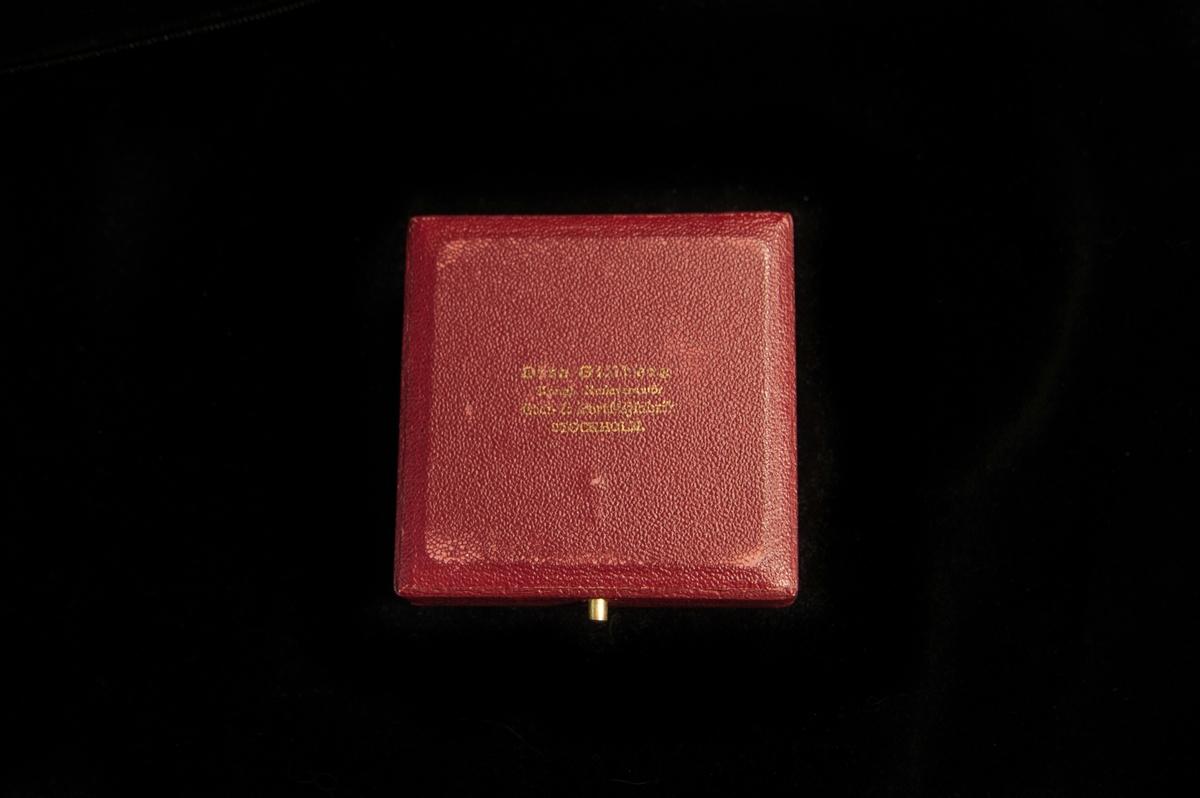 Utställningsmedalj av guldfärgad metall, förvarad i ask.  Motivet på medaljens åtsida består av en kvinna som spinner lin samt en man som hyvlar i bakgrunden. Asken är klädd i textilpräglad röd papp. I askens lock är det fodrat med gräddvitt siden, och i botten är det fodrat med svart sammet, med ett blågult band för att lufta medaljen ur fördjupningen.  Utdelad vid Skaraborgs läns Hantverks-hemslöjds och Industriutställning i Falköping 1910.