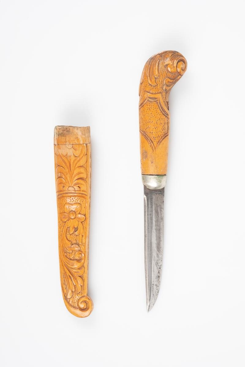 En liten kniv med slire. Skaft og slire er laget av tre, knivbladet er av jern. Treverket er utsmykket med utskjæringer av akantus. Skaftet har et rundt buet hode i enden.