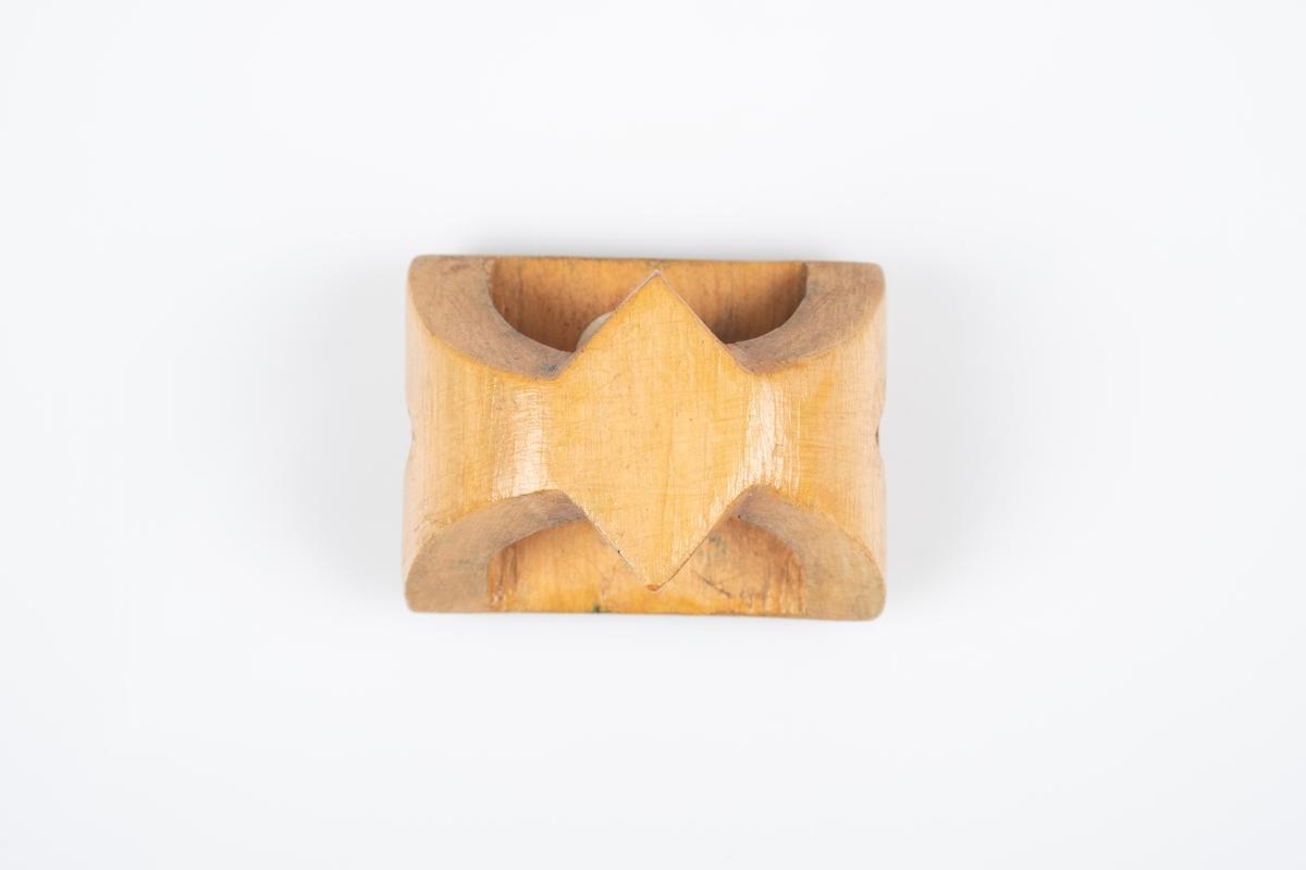 En utskåret serviettring i tre. Framsiden er flat og firkantet med inngravinger av navn og blomst.