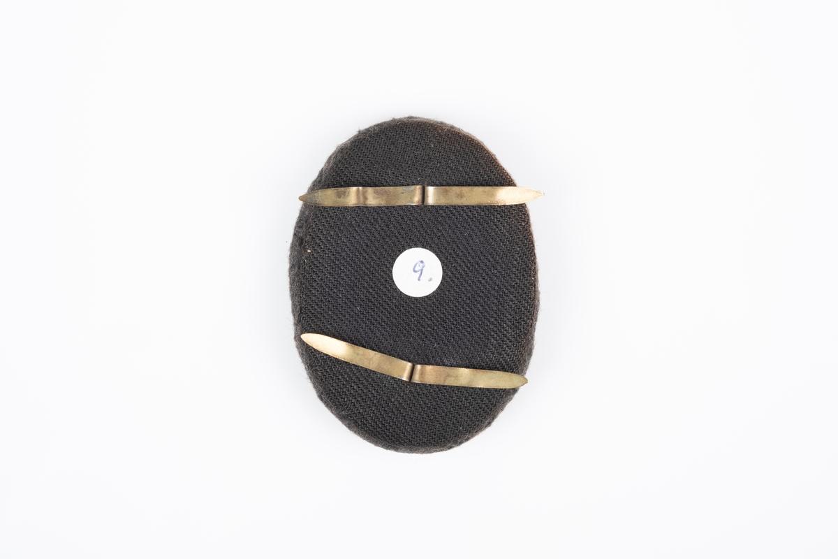 """En medaljong i tekstil med to splittbinders på baksiden. Framsiden har brodering av """"H7"""" med krone, """"Grini"""" og fangenrummer."""
