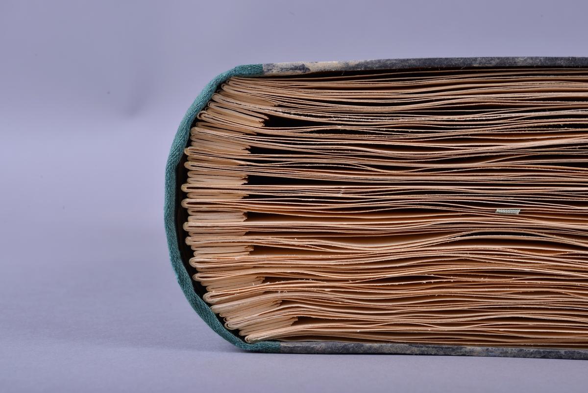 Innbundet bok med punktskrift. Tosidig trykk. Gråsvart omslag av kartong. Forsats av gult papir. Sidene er av gult papir. Tekstilhalvbind; ryggen og hjørnene er forsterket med grønn tekstil.