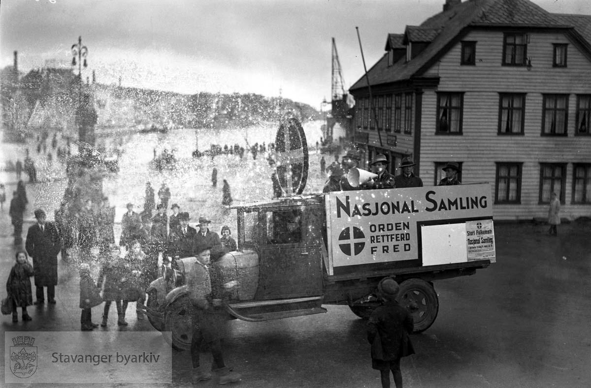 NS, Nasjonal Samling på torget mot vågen.Lastebil med velklingende, salgbare slagord..Bilen og folkene er der for å reklamere for et stort folkemøte (se plakat nederst til høyre på lasteplanet)