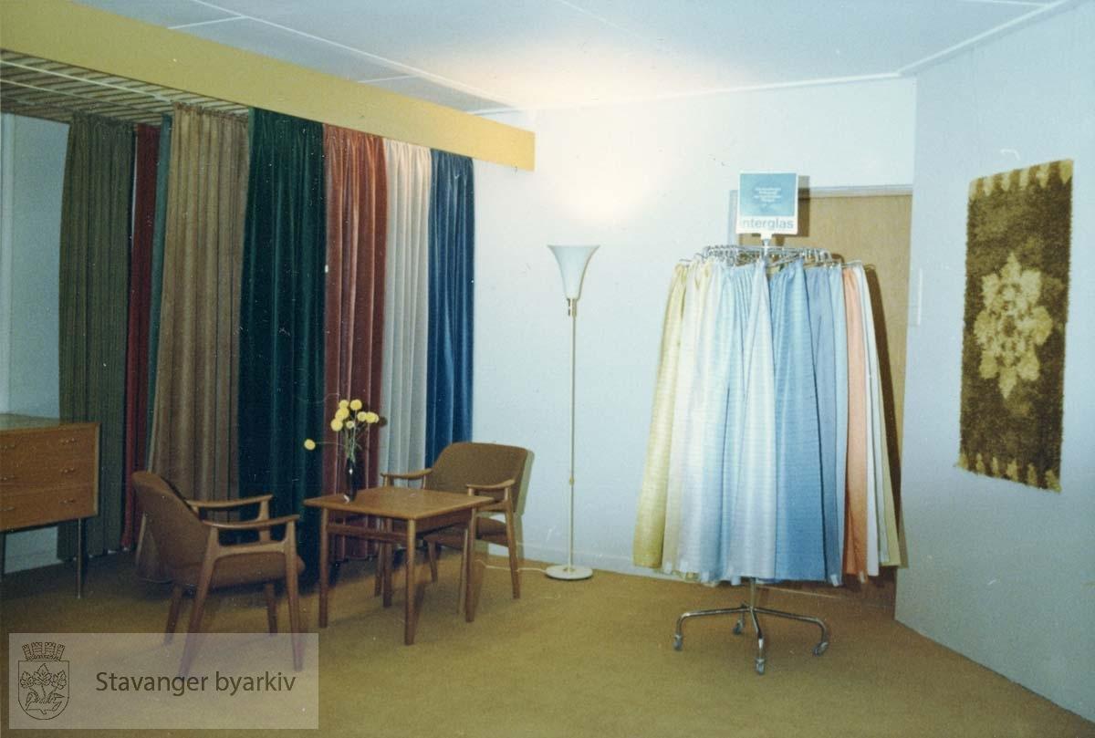Butikkinteriør i Kirkegaten 22. Presentasjon av gardiner. Stoler og bord, stålampe og veggteppe. Samme foto som BtSt2011_01_034 i svart hvitt. Utskilt fra PA293.
