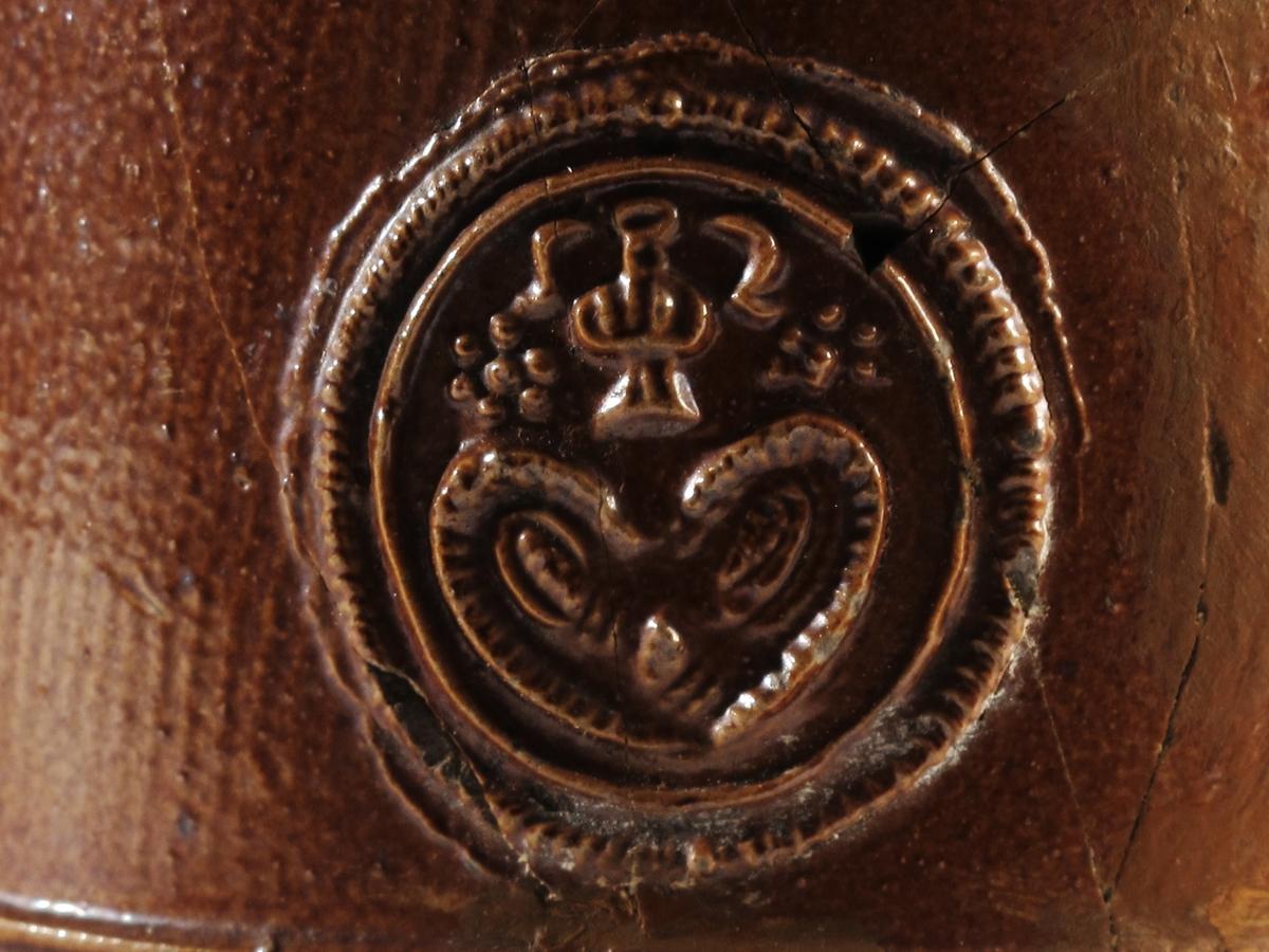 Stentøykrus m. lokk av sølv, 1700 årenes siste del. Profilert, rundet kant m. forholdsvis bred brem,  radiært riflet, på toppen mynt i radiært riflet  innramning, deretter tunget sirkel og nærmest punsling, stående blad m. opprullede fliker som lokkgrep. På mynten portrettbyste og tekst , revers side har kronet riksvåben, 1732, 24 skilling danske. Sølvsmedstempel.  Lokket montert på brunt stentøykrus, stripete og  glatte feldt, midt på ornert stempel, øverst nuppet  feldt.   Tilst juni 1961: Kruset knust og limt, lokket dårlig festet.