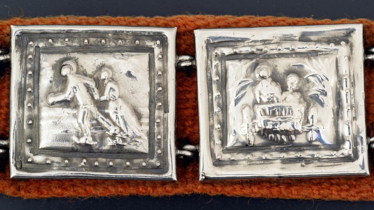 Grovt ulltøy over strie,hekte av sølv, 2 hjerteformede stykker. Forgylt plate med dekor, kvadratisk metall- plate. Drevet arbeide, med figurer. Forgylt plate med filigran. Kvadratiske plater med figurer i landskap, alle forskjellige. Platene er laget av Otto Valstad og forteller om ham og Tilla Valstad.