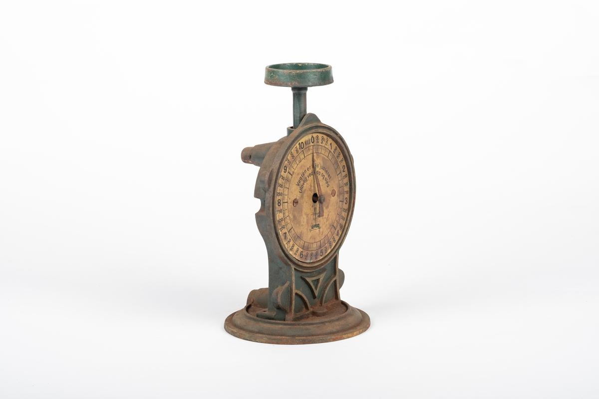 Vekten består av en rund fot og en skive med viser. Skiven er festet til et stativ på foten, der de ulike delene er skrudd sammen. Stangen som skal holde vektskålen går ned i stativet.