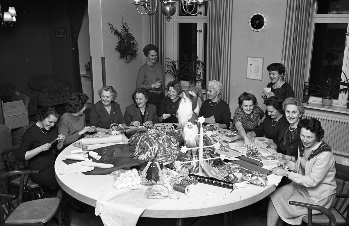 Lions damer julpysslar Runt bordet, från vänster: Berit Munkberg, Siw Rudengård, Lilly Hedlund, Ella Högfeldt, Ingrid Hell-Carlsson (stående), Siri Wallström, Hill Eklöf, okänd, Ulla Björklund (stående), okänd, Gulli Lutteman och Märta Frising På bordet ligger silkepapper, snören, julpapper, julgranskarameller, tomma hushållsrullar och bomullstussar. Mitt på bordet står två skäggiga tomtar. Platsen kan vara Stadskällaren