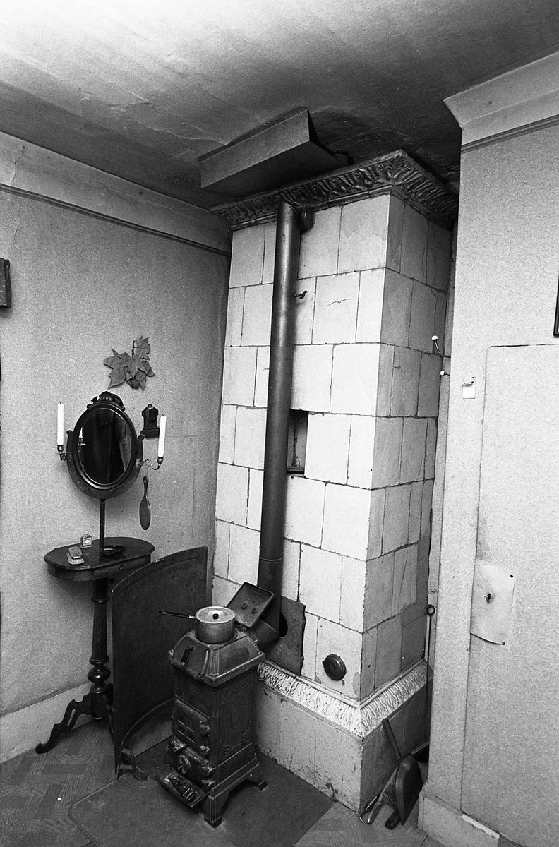 Interiör. Kvarteret Tullnären, mellan Storgatan - Trädgårdsgatan och Herrgårdsgatan - Paradisgränd. Bostad med kakelugn och kamin. Ett pelarbord med spegel.
