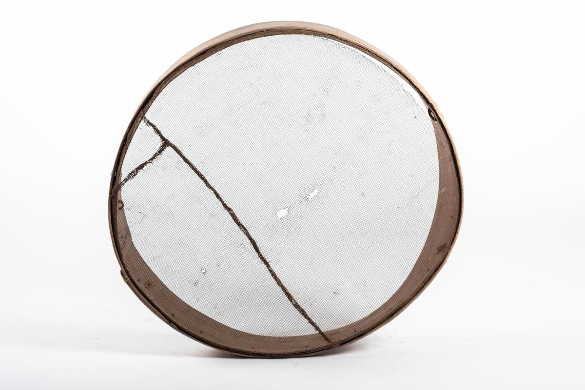 Stort, rundt såld med stålnettingbunn. Rammen består av to ringer, hvor den ene er større enn den andre. og begge festet med tegersøm. Rester etter vidjespenninger tre steder (håndtak?)