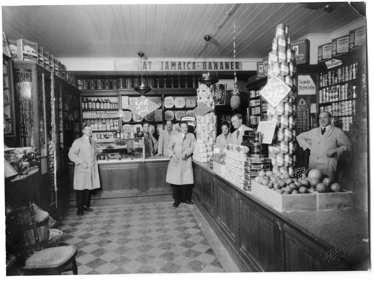 Handelsbod med sju personer i personalen. Alla är klädda i arbetsrock. Här säljs tvättmedlet Tvätt-Björn, julgransljus och även bananer. Varorna är staplade i pyramider på disken. Lanthandel (Den första bananlasten kom till Sverige i november 1944)